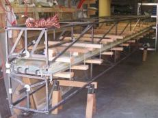 """The bonding done, we clamp the two molds together with 2x4s on 13 spanwise stations, 26 one-foot chunks of 3/8"""" allthread, and 52 nuts and washers."""